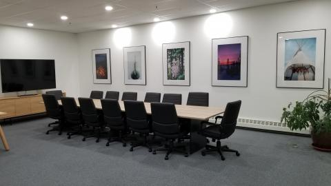 The finished boardroom, complete with table, chairs, and beautiful photos on the walls.