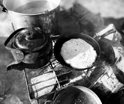 Cooking bannock over the fire. Photo Credit: WLWB Staff.
